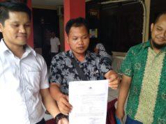 foto Moh Hosen saat menunjukkan surat dari kepolisian (foto: POJOKSURAMADU.COM)